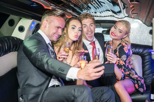Excited Friends With Champagne Flutes Taking Selfie In Limo